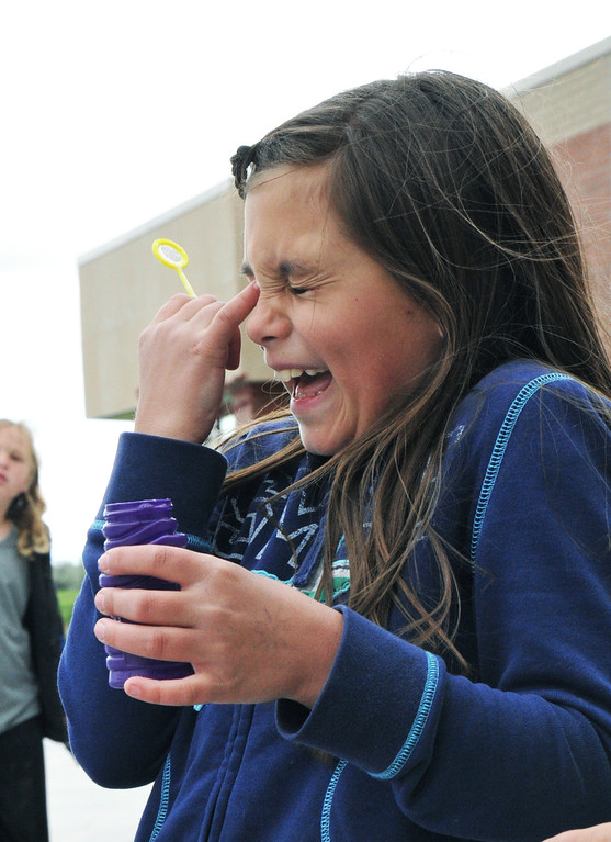 Victoria Greenelsh, third grade, laughs as she wipes off a bubble that blew back into her face during Tuesday's early release fun day at Big Horn Elementary School. June 4, 2013. (The Sheridan Press/Justin Sheely)