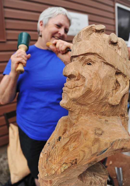 "Smiles are shared as Pam Willis carves ""The Court Jester"" during Story Days Saturday. Willis is part of the Wood Carvers of the Big Horns, who were showing their work in hopes of attracting the next generation of wood carvers. (The Sheridan Press/Justin Sheely)"