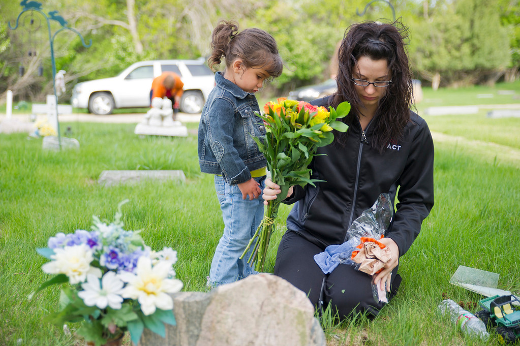 2-year-old Kinley Hale stands next to her mother Nichole Hale as they clean a headstone that belongs to a friend Wednesday, May 22, 2013, in the children's section of the Sheridan Municipal Cemetery. (The Sheridan Press/Justin Sheely)
