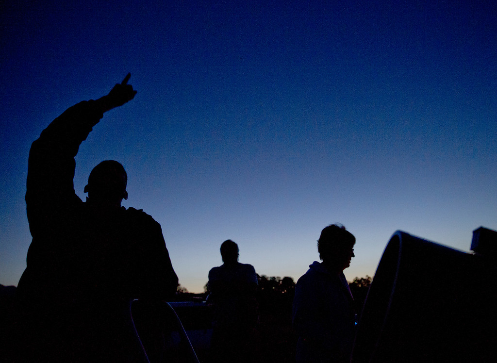 Science Kids Instructor Samuel Singer, left, points to the sky during the Stargazing class Tuesday night at the Brinton Museum in Big Horn. Singer, who has a doctorate in Science Education from the University of Wyoming, guided the students through the night sky with his telescopes and laser-pointer. (The Sheridan Press/Justin Sheely)