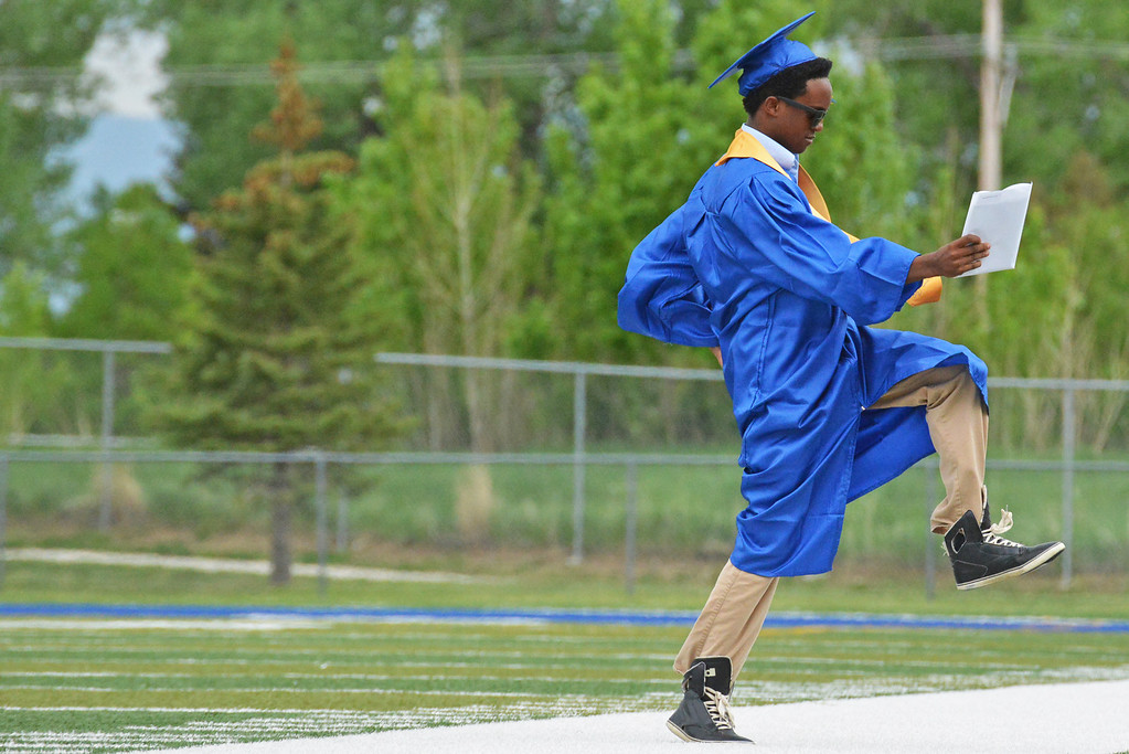 Malik Grant gives a celebratory fist pump as he walks off Scott Field with his diploma Sunday afternoon. (Brad Estes/The Sheridan Press)