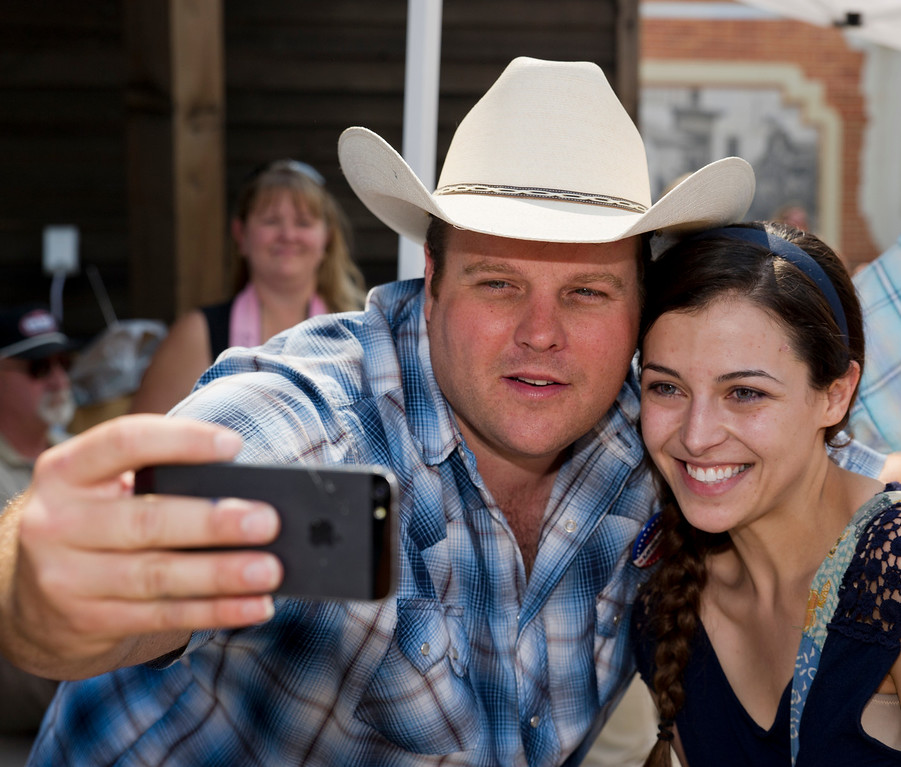 Actor Adam Bartley (The Ferg) takes a picture with an iPhone of himself and Rachel Wear of Buffalo during Longmire Days at the Crazy Woman Square in Buffalo. August 17, 2013. (The Sheridan Press/Justin Sheely)
