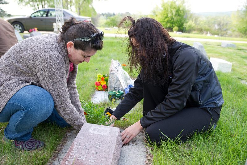 Shebree Moore, left, plants a flower with Nichole Hale Wednesday at the children's section in the Sheridan Municipal Cemetery. Moore and Hale are friends with a family who has a child buried here.