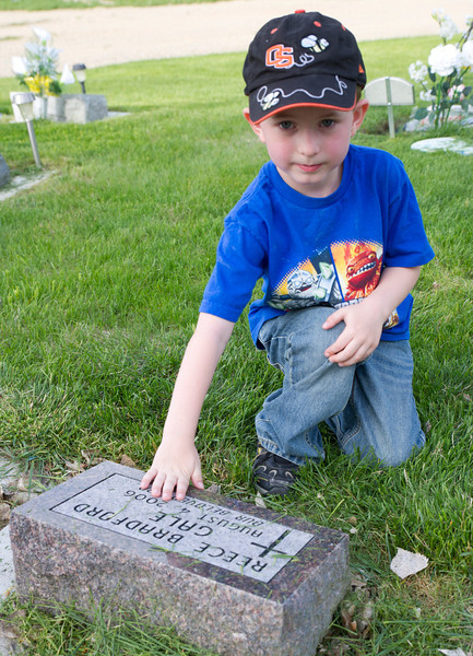 "Ian Gale, 5, places his hand over his brother's headstone Wednesday evening at the children's section at the Sheridan Municipal Cemetery. ""Let me introduce you to my brother."" Said Gale, as he walked up to me. Ian led me to a headstone where he knelt down. Justin Sheely/Sheridan Press."