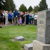 The group stands among the headstones during the tour at the Sheridan Municipal Cemetery Tuesday evening.