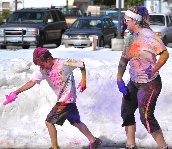 Nine-year-old Eli Cummins, left, runs away as Elana Ostler, 17, makes a revenge attack with blue powder after finishing the Combat Color fun run at Sheridan College on Sunday.