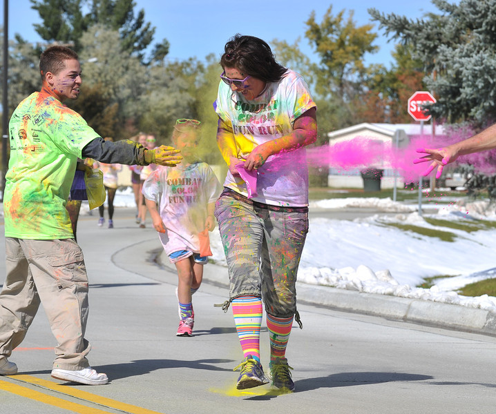 Sherrie Reish runs as color powder is thrown at her during the Combat Color fun run at Sheridan College on Sunday.