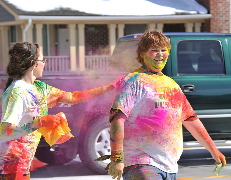 Leanna Bass, left, slaps her brother David Britton with a dose of color powder after finishing the Combat Color fun run at the Sheridan College on Sunday.