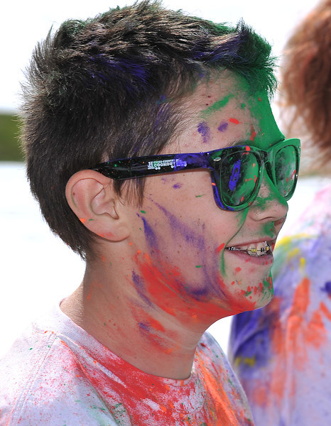 Cade Neeson, 14, runs on after receiving some powder in the face during the Combat Color fun run Sunday at Sheridan College.
