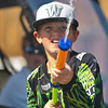 Cade Reish, 6th grade, sprays the crowds with a water gun during the Dayton Parade Saturday in Dayton.