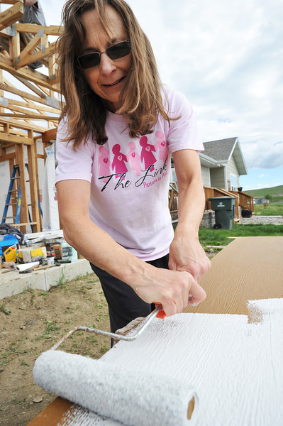 """Mary Grant rolls paint onto a panel of siding Saturday morning for the Habitat for Humanity project on Poplar Trail. This was Grant's first time volunteering for Habitat for Humanity. Saturday's project was marketed as """"Women Build,"""" to encourage volunteering for Habitat for Humanity of the Easter Bighorns."""