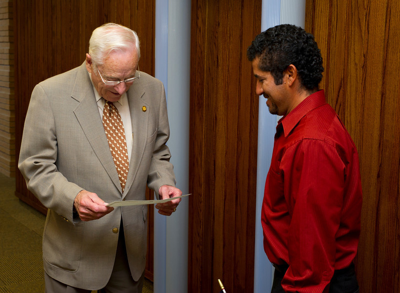Wyoming State Rep. John Patton looks at Jhony Lima's Certificate of Naturalization after attending the Naturalization Ceremony Friday at the Sheridan County District Court.