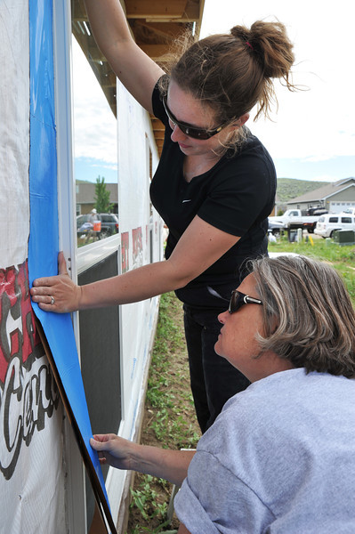 """Meghan Nedwick, left, and Nancy Marchese apply weather seal to a window for Habitat for Humanity of the Eastern Bighorns """"Women Build"""" Saturday on Poplar Avenue. """"Any one can build."""" Said Matt Davis, Executive Director of Habitat for Humanity of the Eastern Big Horns. """"A volunteer is a volunteer – it doesn't matter what gender you are."""""""