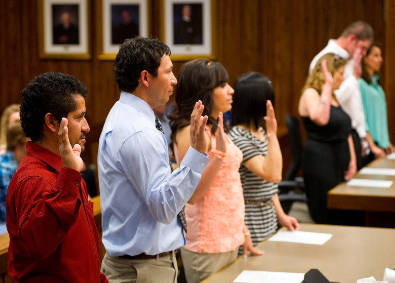 Naturalized American Citizens raise their hands as they take the Oath of Allegiance during the Naturalization Ceremony Friday Morning in the District Court at the Sheridan County Courthouse