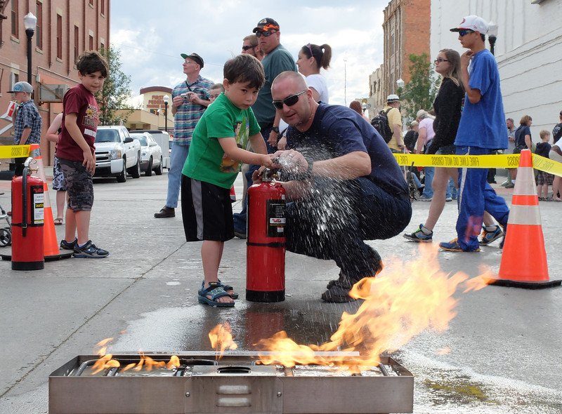Benjamin Bujans, 4, uses a fire extinguisher with Fire Fighter Kyle Johnson to put out a fire during Third Thursday on Main Street. The Sheridan Fire-Rescue Department used a Fire Extinguisher Training Burner and a water-filled fire extinguisher to demonstrate how to put out fires.