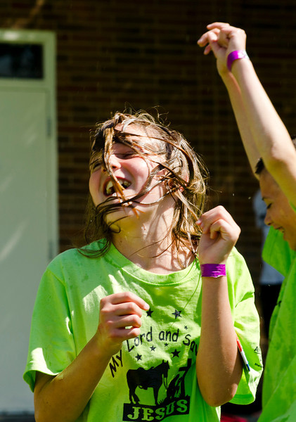 Taylor Beatty, 10, whips her hair after dunking her head in a bucket of water during Vacation Bible School Wednesday at the YMCA. This is the 27th year that the YMCA has hosted VBS, which is organized by 13 different churches and also a number of businesses and organizations in the Sheridan community.