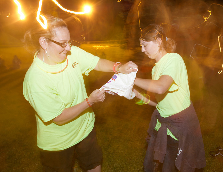 Cynthia Whiteman, left, and her daughter Emma, 14, quickly rip open a folded and frozen t-shirt for the frozen t-shirt contest/race Friday night during Relay for Life at Kendrick Park. Each contestant had to open the frozen t-shirt and wear it as they raced around the loop.