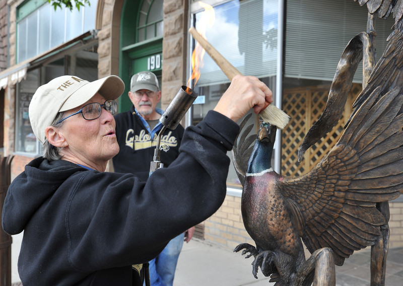 Debbie Bakel applies a conservator's wax on a sculpture after heating the metal with a torch with her husband Richard Bakel Tuesday morning on Main Street. The Bakels does sculpture maintenance on the public arts in Sheridan every year on the first week of June.
