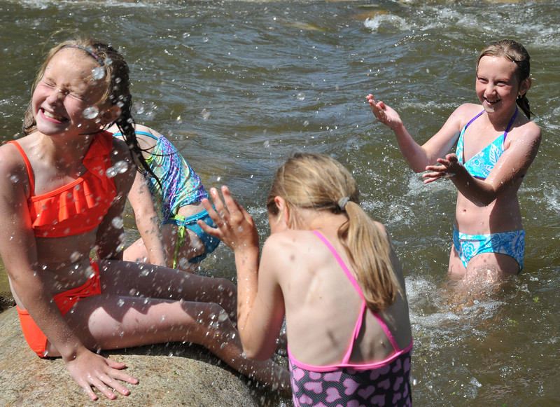 10-year-old Taylor Larsen, left, turns away as she and her friends are splashed by Marisa Nichollas, 10, in the Big Goose Creek Thursday afternoon at Kendrick Park.