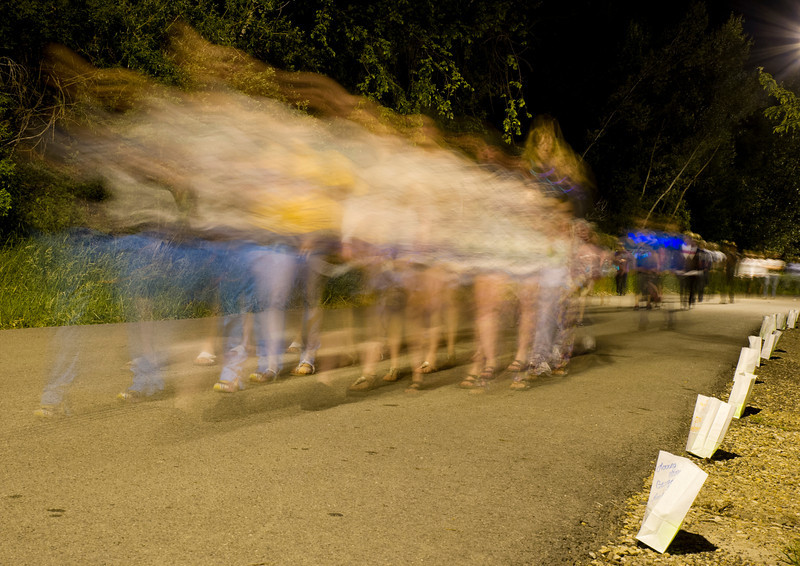Late-night walkers make a lap around the circle of luminaries during Relay for Life Friday night at Kendrick Park.