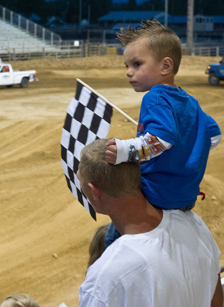 Ryan Lanz, 2, holds a flag as he sits on Drell Amende's shoulders during the Monster Truck Show by Mega Promotions Saturday at the Sheridan County Fairgrounds.