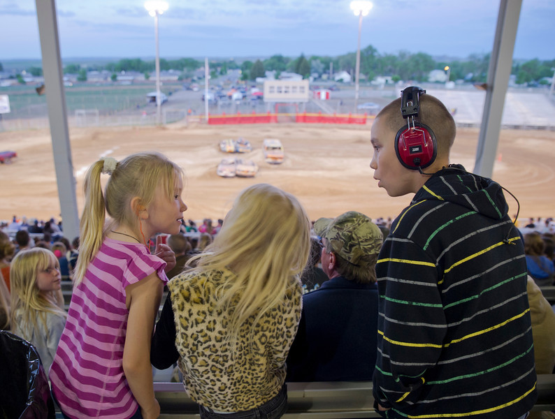 Children watch the Monster Truck Show standing behind the seats on Saturday at the Sheridan County Fairgrounds arena. From left, Mary Thompson, 8, Jaeli Klein, 8, and Matthew Thompson, 11.
