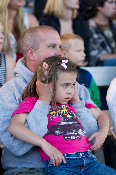 Andy Irion covers the ears of his 6-year-old daughter Aubree Saturday night during the Monster Truck Show at the Sheridan County Fairgrounds.