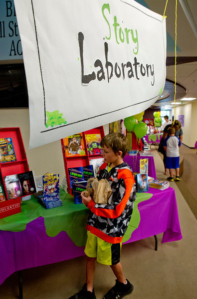 Summer School fourth grader Triston Johnson explores the Book Fair Wednesday at Woodland Park Elementary School. To help encourage reading, the summer school students were allowed to choose 6 free books to take home.