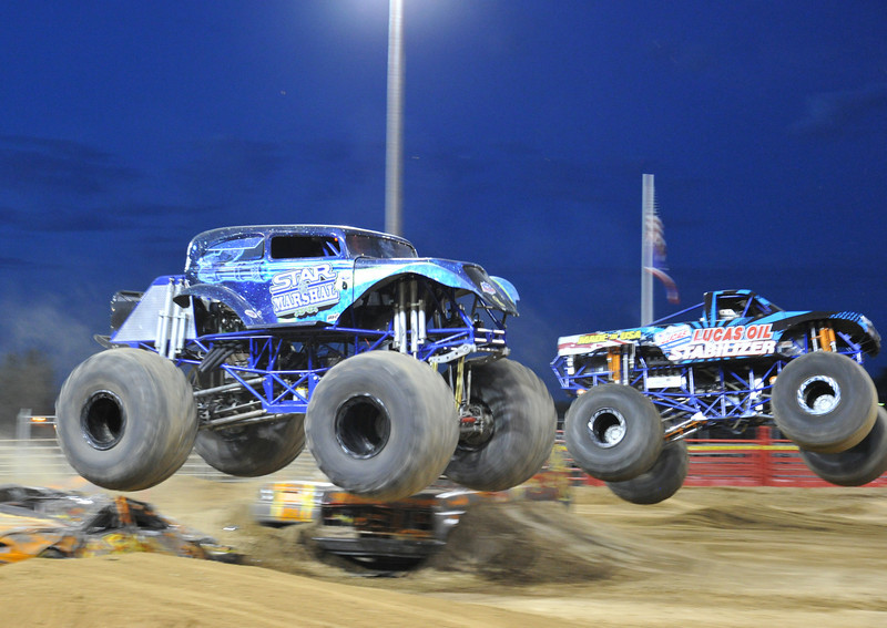Sponsored monster trucks race each other on a jump for the crowd's amusement during Saturday's Monster Truck Show at the Sheridan County Fair Grounds.