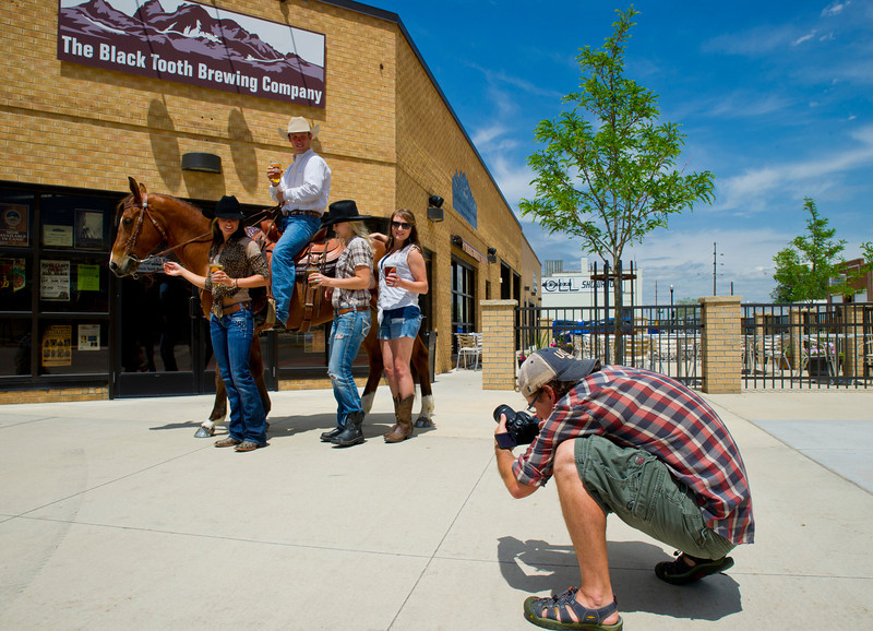 Leon Schatz gets a low angle during a promotional photo shoot with Gunny, a Quarter Horse, at the Black Tooth Brewing Company on Tuesday.
