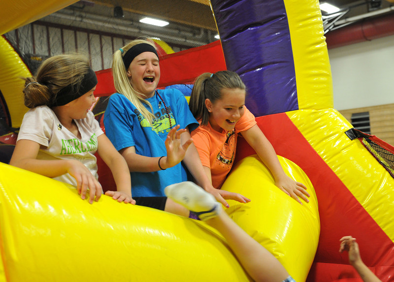 Third graders Shelby Atkinson, left, Madison Blaney, and Anna Melin, right, play on an inflatable ride during the early release fun day Tuesday morning at Big Horn Elementary School. The school celebrated the end of the school year with fun activities for the students before being dismissed early.