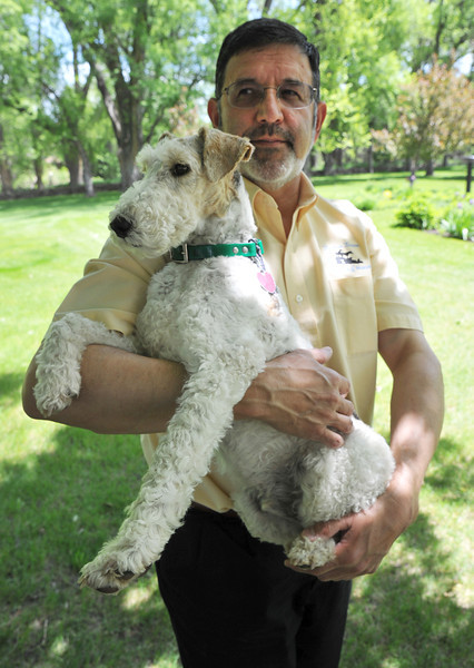 Ken Schuster holds Dickens, a Wirehaired Fox Terrier, outside the Brinton Museum Thursday. Dickens has made a full recovery after being run over by a motor vehicle last January.