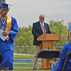 Commencement speaker Doug Raney waits for SHS 2013 valedictorian Jin Woo Kim to take his seat Sunday afternoon at Scott Field.