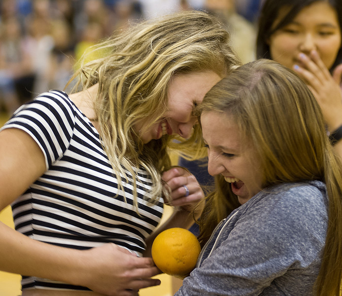 Sara VonKrosigk, left, and Kellie Kekich react as they fail to pass the orange during a game at the homecoming assembly in the Sheridan High School gymnasium. The students in each grade competed with each other by playing a game of passing the orange without using hands.