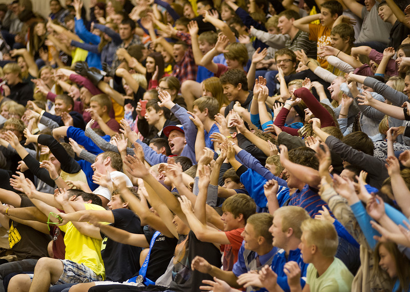 Students wave their arms together during the team spirit cheer at the homecoming assembly Thursday at the Sheridan High School gym.