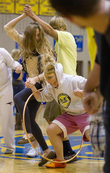 Seniors Sarah LeTempt, left, slides the hula-hoop to Drew Dafoe in a race against the other grade students during homecoming assembly at Sheridan High School. The students formed a human chain and were not allowed to break hands while passing the hula-hoop.