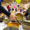 "A huge collection of handcrafted and painted bowls are set out on a table for guests to use for dinner at the ""Filling an Empty Bowl"" fundraiser for the VOA Homeless Shelter on Thursday. The event had 786 bowls donated by the students of the community."