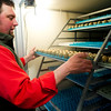 Darrell Meineke pushes a tray of eggs into a slot inside the Incubator on Friday of last week at the Bird Farm.