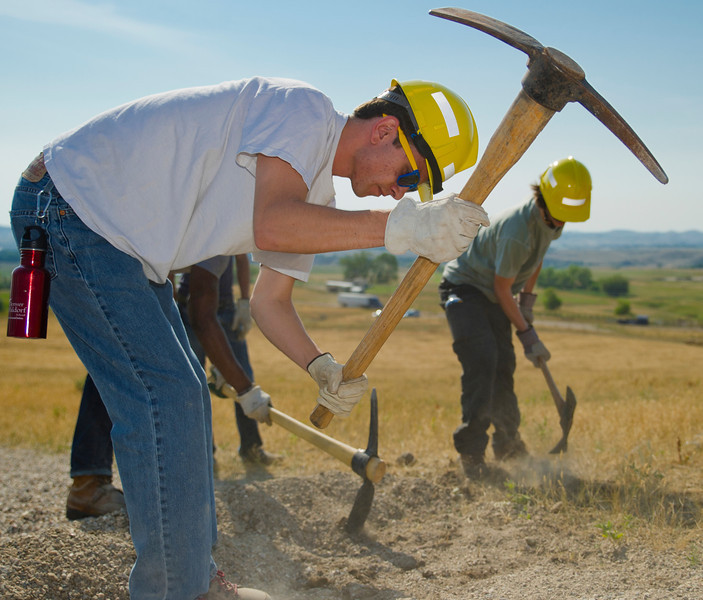 Up with People volunteer Miles Justice, from Denver, Colo., chips away with a pick axe Tuesday at the Soldier Ridge Trail at the end of West Fifth Street. Justice and a crew of volunteers from Up with People worked with the Sheridan County Land Trust to dig a series of rolling dips in the trail for water erosion control.