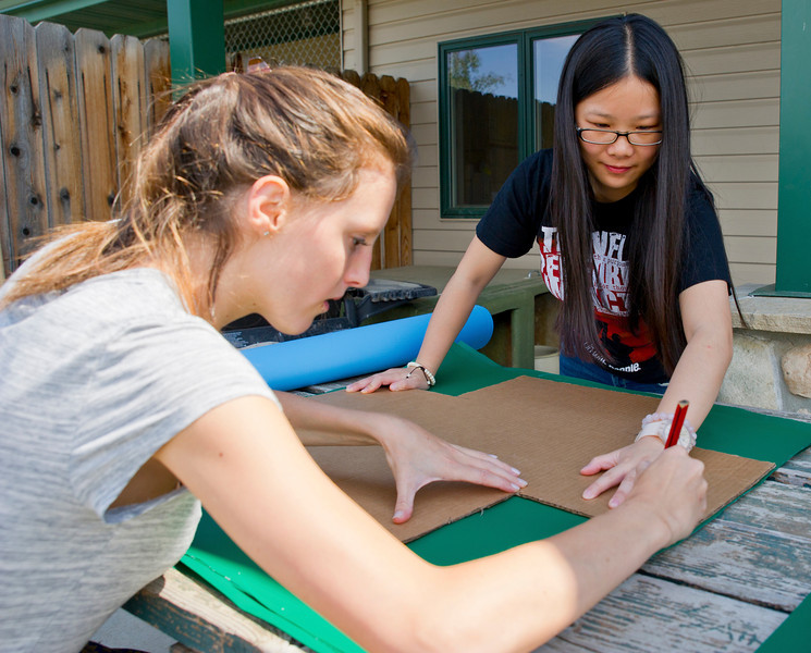Up with People Volunteers Apolline Mourlon Beernaert, left, of Belgium, and Ling Yue Li, of Shanghai, China, trace out cut lines on pieces of fabric for making elevated cat beds Tuesday at the Dog and Cat Shelter. This is Mourlon Beernaert and Li's first time serving Up with People and Li's first visit to the United States.