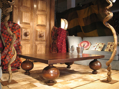 One of many arrangements in the artmosphere showroom set up by Julian Maison and Marcel Maison. The Coffee table made from our antique reclaimed hard wood collection in Brasil we called it the Onion table. to eeather side is artwork by Monica Carvalho who makes art using natural seed,pods and other items from the Amazon in this case vines. in the back a custom made sofa with pillows we made from Uzbek antique Uzbek suani fabrics and in the back ground our huge door also from reclaimed wood with oversides knobs.