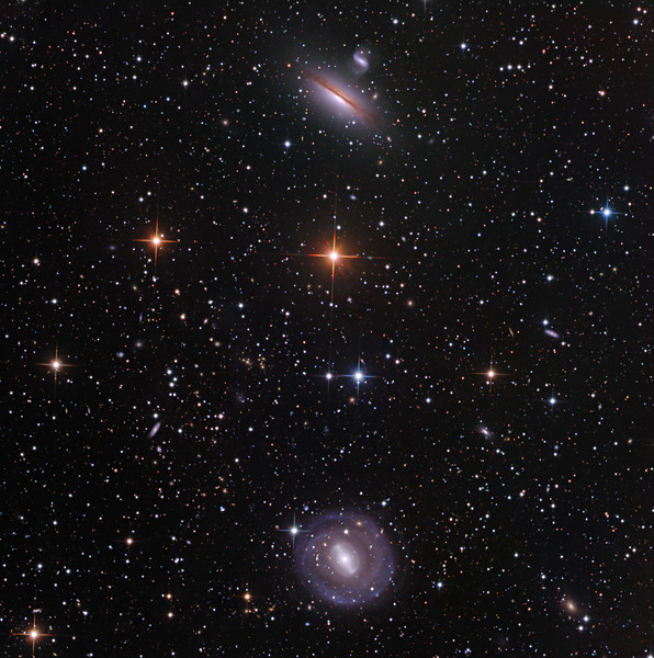 "NGC 5101 and 5078 in southern Hydra, and literally hundreds of distant friends. There is a nice cluster of distant orange galaxies about 20% of the way toward 8 o'clock from centre. 5101 is a delicate face-on spiral. 5078 is an edge-on spiral with branching dust lanes across the more orange centre, and interacting with a companion. <br /> <br /> Lum 7 hrs in 1hr subs. RGB 2.5hrs each in 30 min subs. Aspen CG16M on 20"" PlaneWave. As always, all processing using our own in-house software, GoodLook 64."