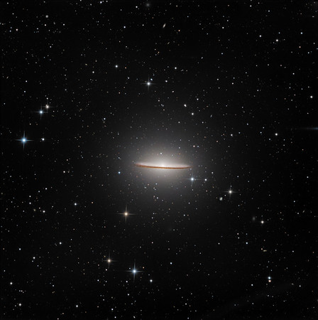 Sombrero galaxy M104 in Corvus.  Luminance 5.5 hrs, RGB 45 mins each. Note (a) the generally warm colour expected of an elliptical galaxy with a young spiral embedded in it. (b) The huge halo, consistent with the above. (c) The tiny, almost stellar core. These last two are easy to miss if one uses too much contrast, as the outer halo is lost, while the core blows out and looks bigger.  Aspen CG16M on 20 inch PlanWave. 15 minute subs to avoid burning out the core. All processing with our own GoodLook 64.