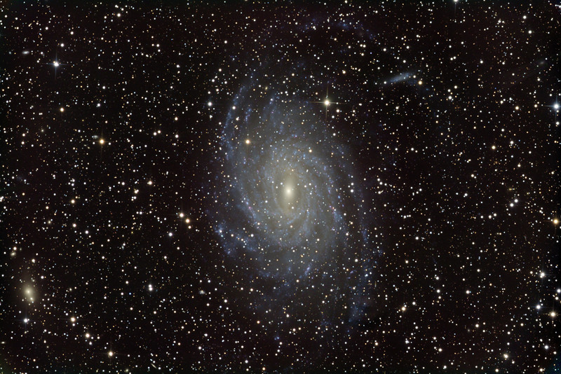 "NGC 6744 in Pavo. A huge (about 24 min arc top-to-bottom) very bright (mag 8.5) delicate face-on barred spiral. Because it has such a large area the surface brightness is quite low (about mag 14/sq arc min), not much above the airglow, making the northern spiral arm (which scrapes the top of the image) very hard to photograph. The main galaxy is interacting with a Magellanic style irregular companion at 2pm. There are many dozens of small background galaxies discernible. North up. Monochrome 10 hrs, RGB 2 hrs each.<br /> <br /> STL-11000M on 20"" PlaneWave CDK on MI-750 fork. All control electronics, firmware, and software, and all image processing software, done in house."