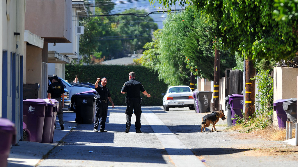 . The F&M Bank at 23rd and Bellflower was robbed around noon in Long Beach, CA on Tuesday, October 1, 2013 and the suspect got away with an undisclosed amount of cash.  Officers and a K-9 unit search an alley behind an apartment complex on 23rd Street. (Photo by Scott Varley, Daily Breeze)