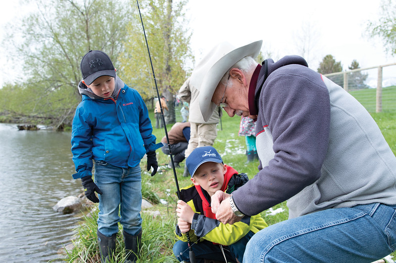 Matthew Gaston | The Sheridan Press<br>Big Horn kindergarteners, from left, Beckett Stewart and Colt Johnson watch as Terry Cram shows them how to bait a hook with nightcrawlers at Wilson Reservoir Thursday, May 23, 2019.