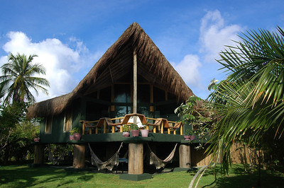 The Restaurant of Butterfly House looks out to the beach and ocean. The veranda's railings double as seating, the roof is a thatched technique from a local palm called Piasava. The columns that hold the building up are painted to look like giant logs from the jungles in the back back of the Hotel.