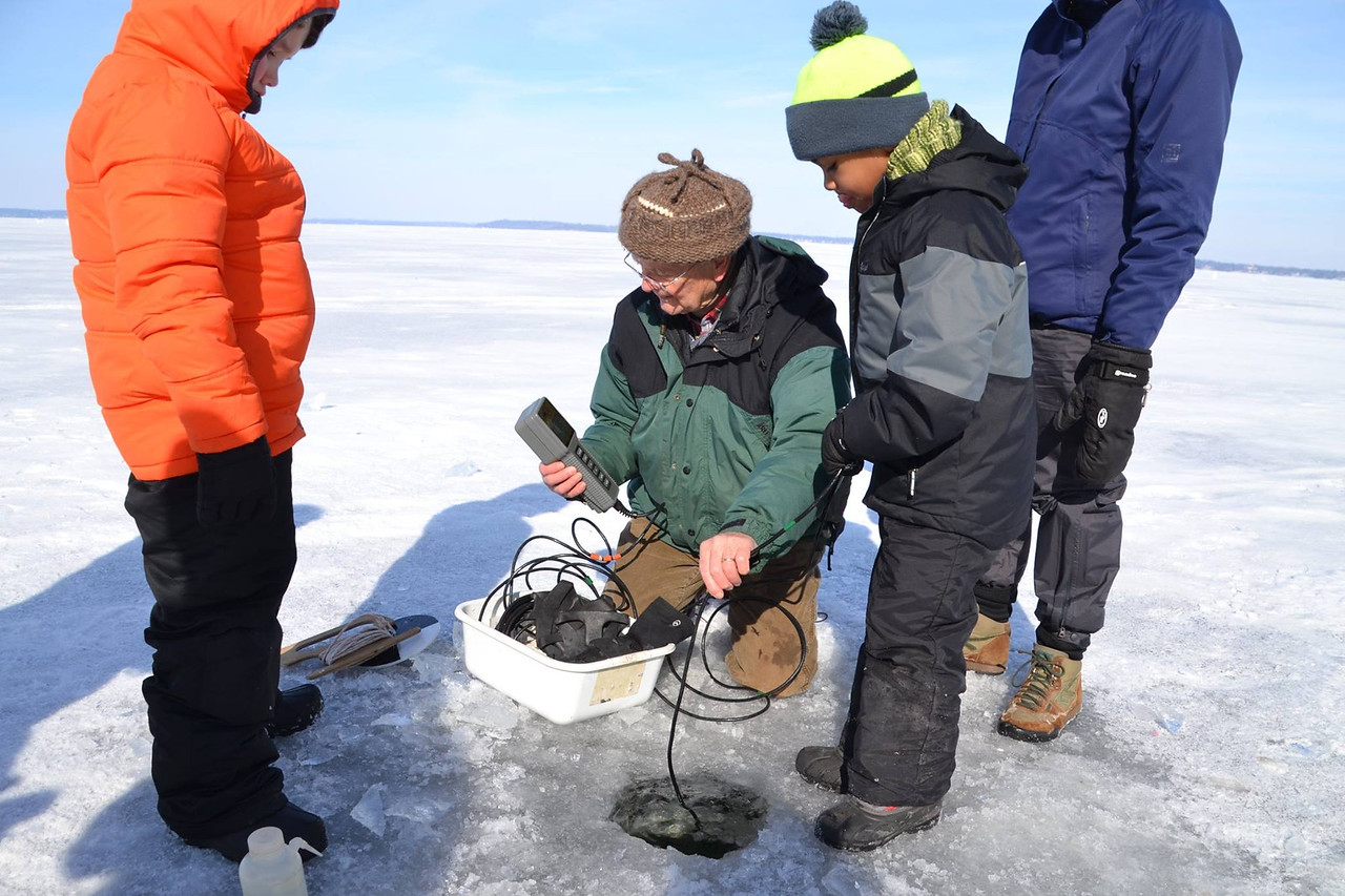 Professor Emeritus of Zoologyand Director Emeritus of the Center for Limnology shows future scientists testing equipment at the ice science lab.