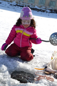 A young scientist clears the water of ice to prepare for tests at the ice science lab.