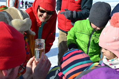 Norma Magnuson looking at ice critters with future scientists at the ice science lab.